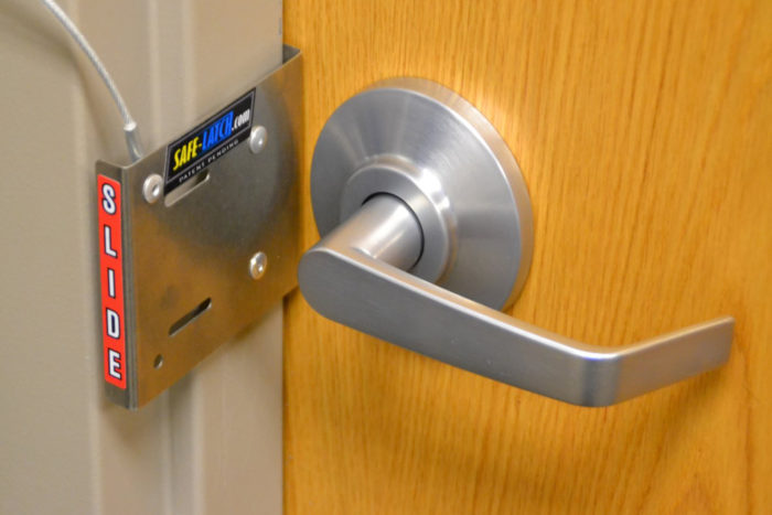 Image of Safe-Latch fast lockdown device in use on out-swing classroom door or office door.