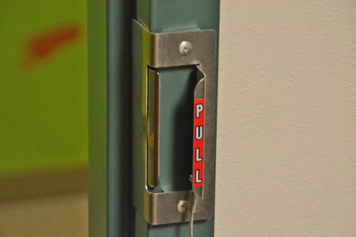 Image of Safe-Latch fast lockdown device in use on in-swing classroom door or office door.